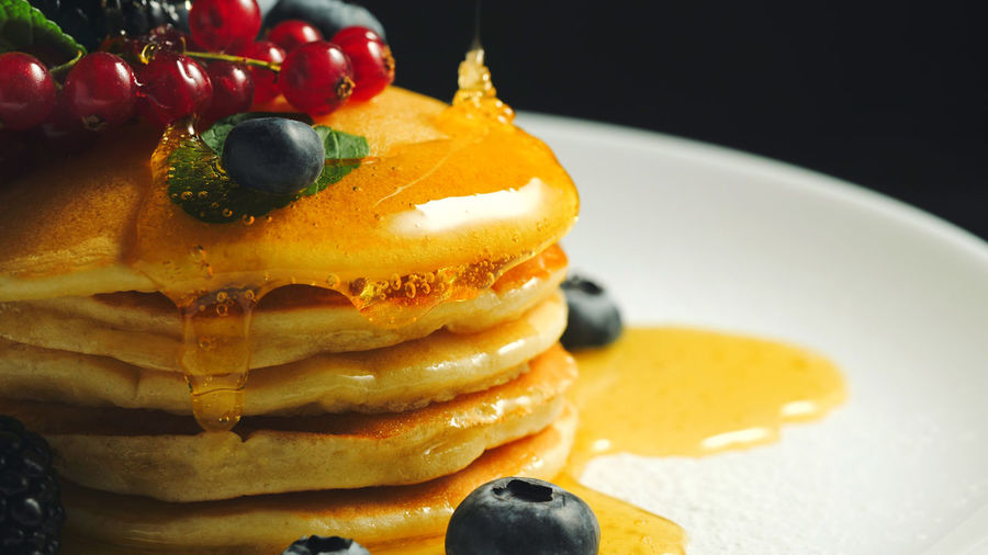 Stack of fresh fluffy pancakes decorated on top with forest berries and pouring honey syrup. Delicious, healthy american breakfast. Fresh bakery concept. Food Food And Drink Fruit Freshness Ready-to-eat Indulgence Sweet Food Sweet Dessert Berry Fruit Close-up Indoors  Plate Cake Healthy Eating Still Life Pancake Temptation No People Garnish Pancakes Breakfast Yummy Dessert Blackberry
