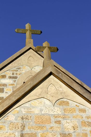 Stone crucifixes set on a church roof in South Australia Australia Church Roof Stone Crucifixes Architecture Building Exterior Built Structure Cross Crucifix Day History Low Angle View No People Outdoors Place Of Worship Religion Sky Spirituality Travel Destinations