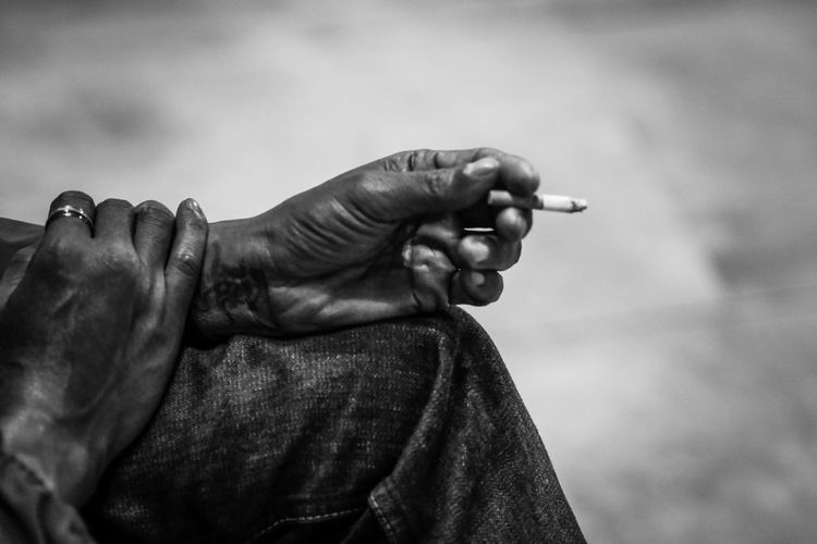 Midsection of person holding cigarette outdoors