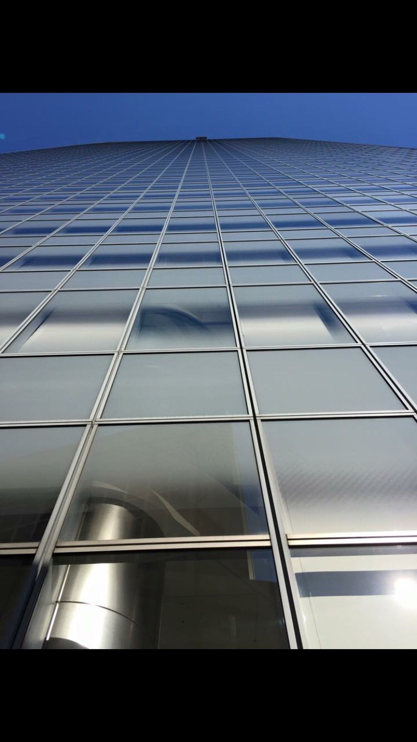 architecture, built structure, low angle view, building exterior, modern, glass - material, window, office building, building, city, reflection, skyscraper, glass, tall - high, sky, transparent, indoors, no people, clear sky, day