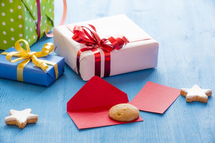 Opened envelope on a blue wooden table, surrounded by gingerbread stars shape cookies and gift boxes Holiday Gifting Celebration Christmas Christmas Decoration Christmas Present Envelope Gift Gingerbread Cookies Sharing Time Still Life Tied Bow