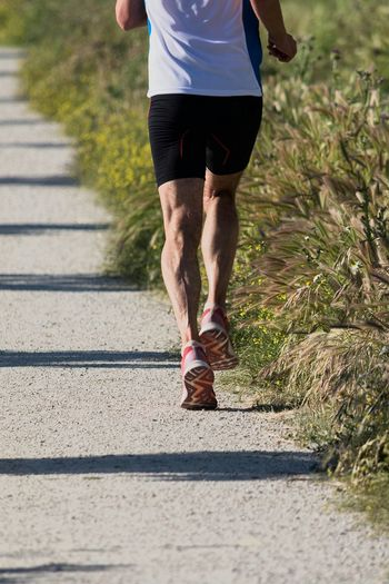 Low Section Of Man Running On Road During Sunny Day