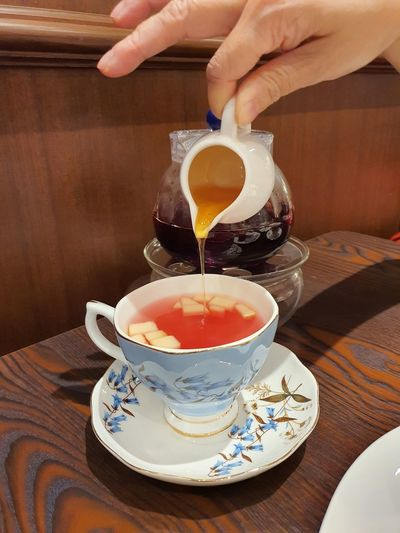 Midsection of person holding tea cup on table