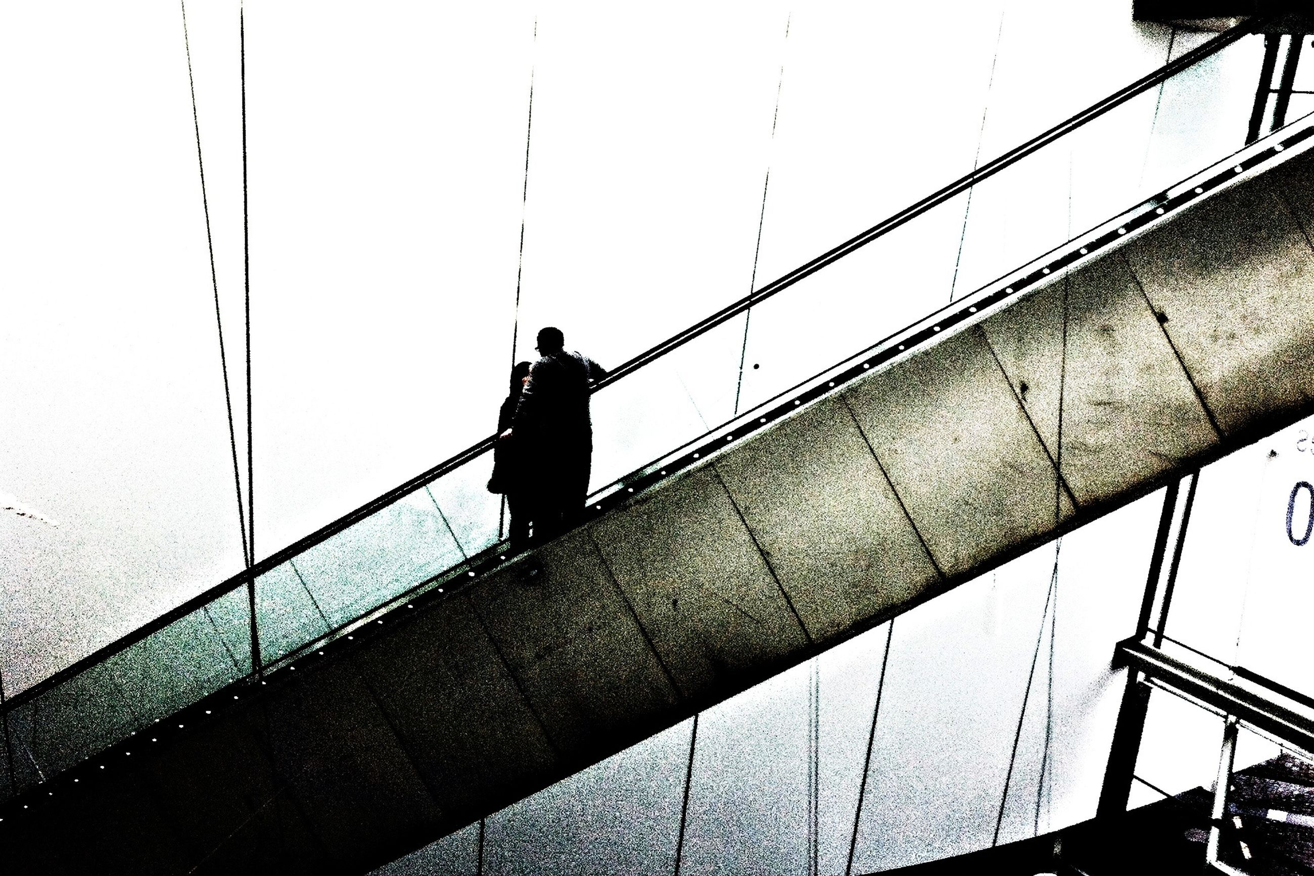 railing, lifestyles, men, leisure activity, low angle view, full length, built structure, standing, silhouette, bridge - man made structure, sky, transportation, metal, architecture, connection, rear view, day