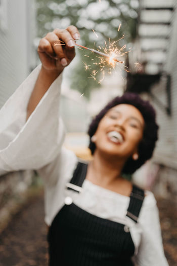 Close-up of woman hand holding lit sparkler