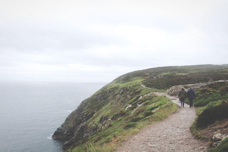 Rear view of people walking on footpath by sea against sky