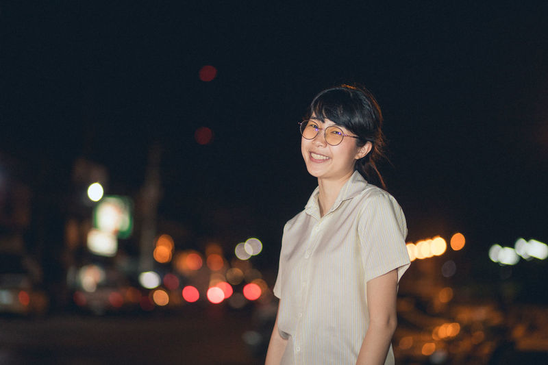 Portrait Of Smiling Young Woman Standing Against Sky In City At Night