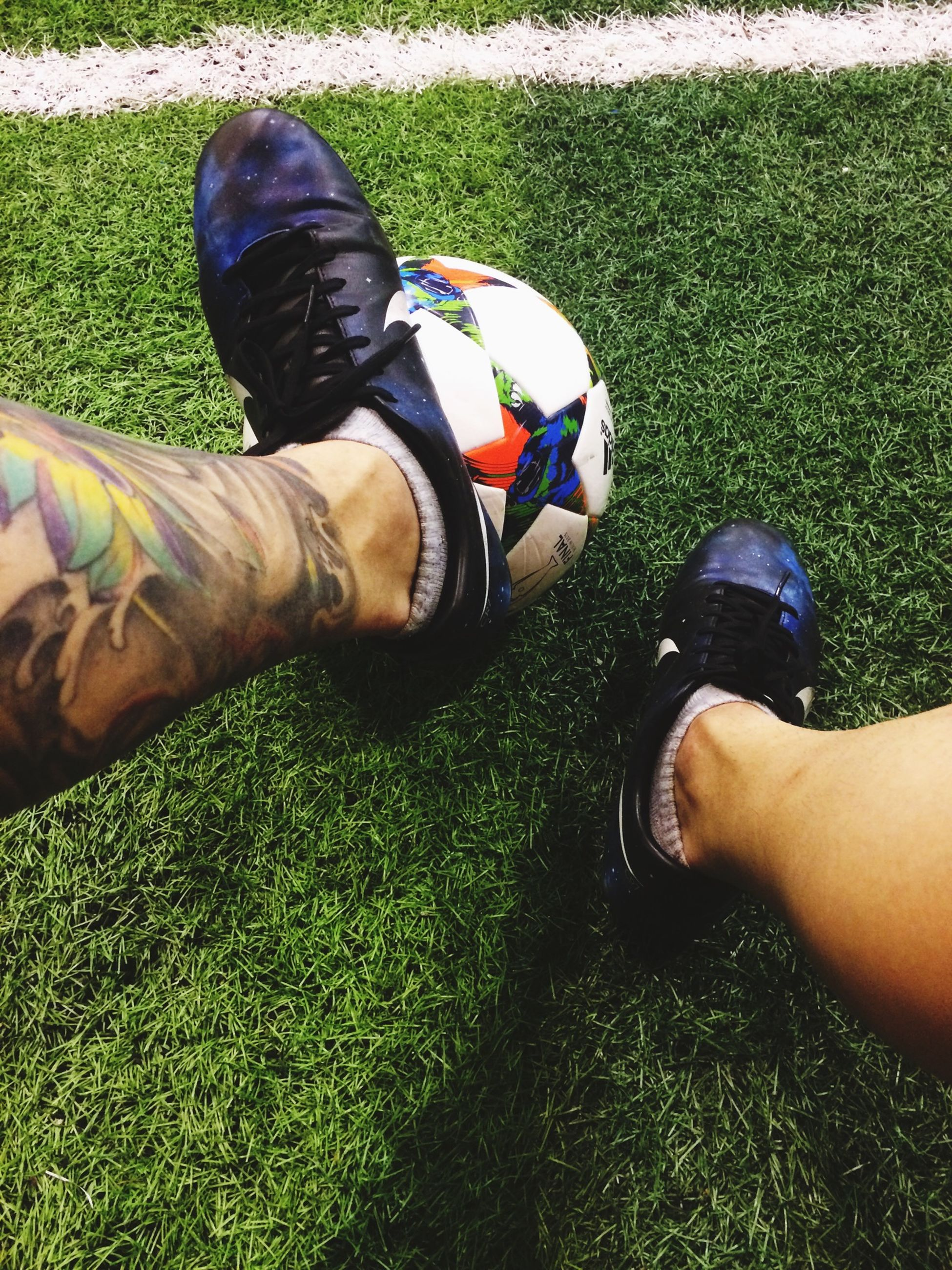low section, lifestyles, person, leisure activity, grass, men, personal perspective, part of, shoe, human foot, high angle view, unrecognizable person, field, holding, grassy