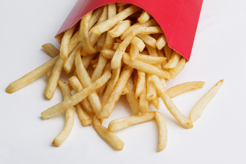 High angle view of meat and fries on white background