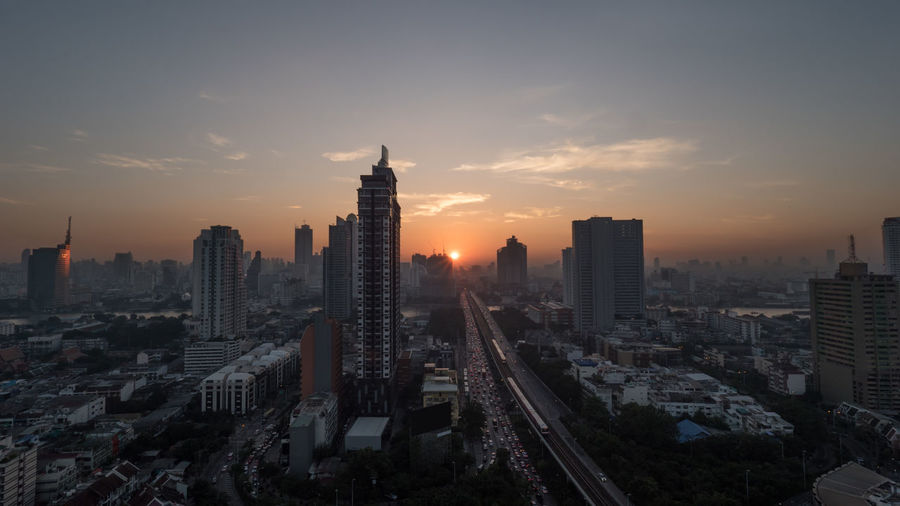 Sunset time in Bangkok, Thailand. City panorama with highrise urban architecture and traffic on highway. Sky in warm colors and sun going down Architecture ASIA Bangkok Car City City Life City Street Cityscape Horizontal Modern Night Outdoors Panorama Road Sun Sunset Thailand Traffic Transportation Travel View