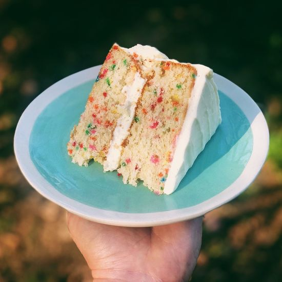 Close-up of hand holding cake