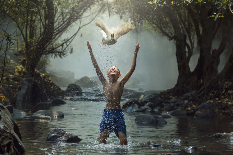 Shirtless boy with arms raised looking at bird flying standing in river