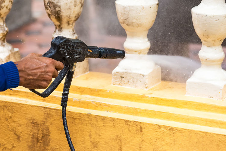 Man cleaning balustrade with water spray