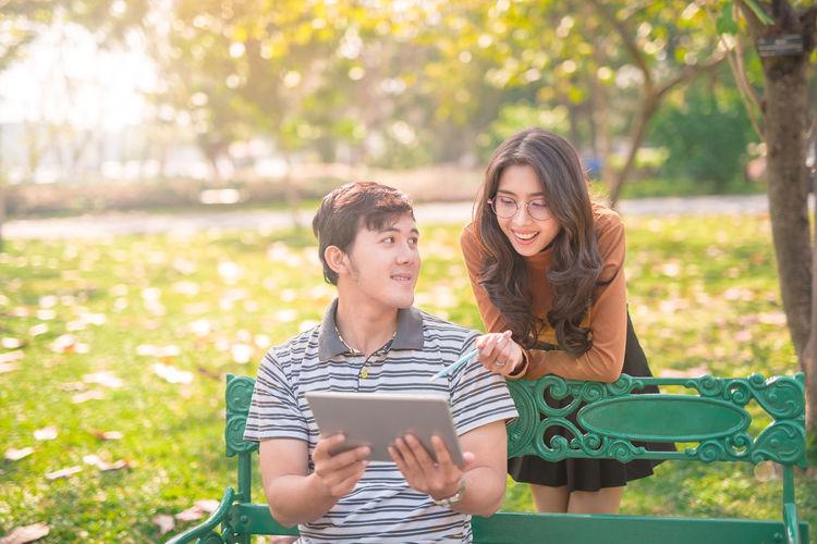 Friends using digital tablet at park