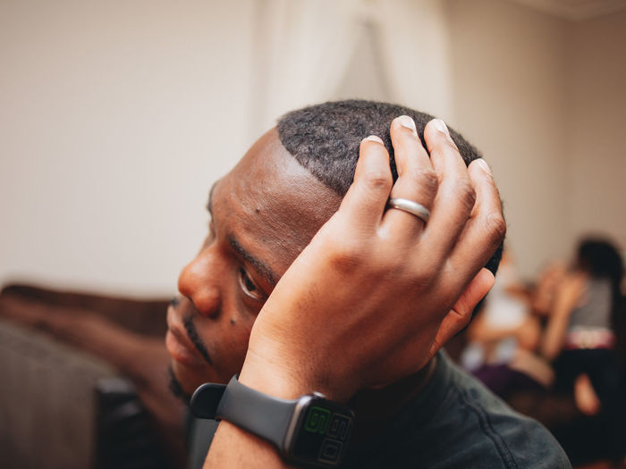 Black man at home looking sad and depressed while mother plays with kids in the background