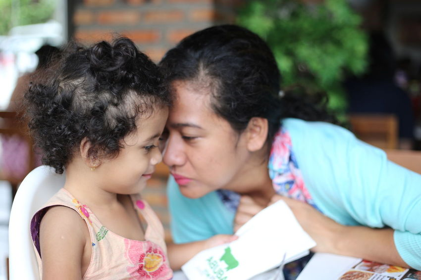 Mom want to kiss her cute curly daughter who seated in high chair in a kitchen of a comfy house Child Childhood Close Up Daughter Domestic Kitchen Domestic Life Family Family With One Child Fun Girls Home Interior Horizontal INDONESIA Indoors  Mother One Parent People Photography Playing Preschool Age Single Mother Two People Women