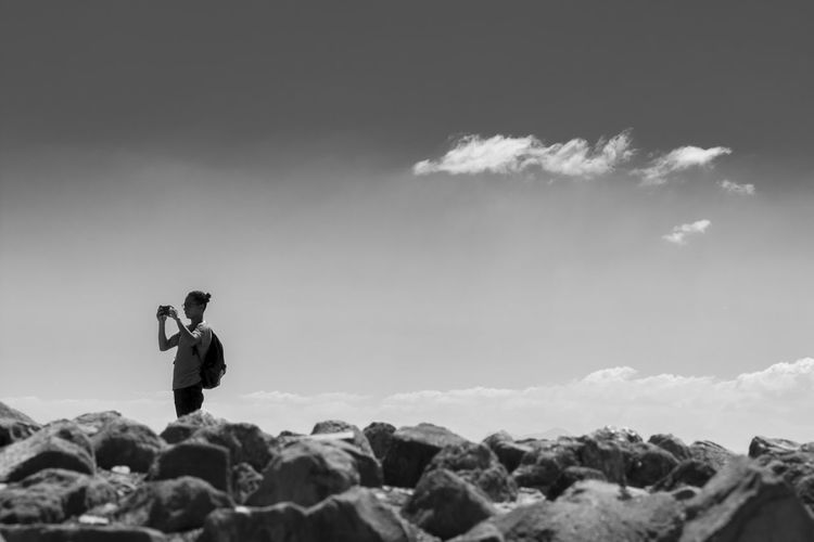Man Photographing By Rocks