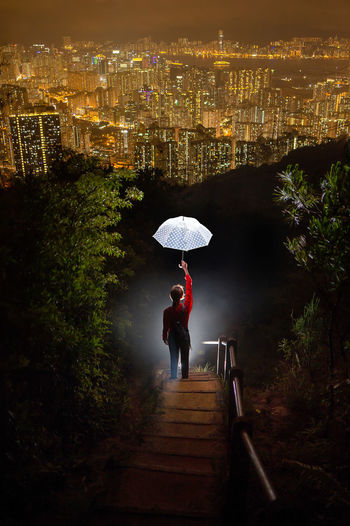Rear View Of Man With Umbrella Against Illuminated Cityscape At Night