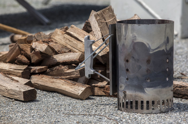 Close-Up Of Camping Stove By Logs On Field