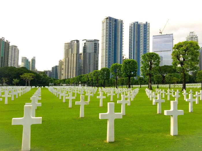 American Cemetery! Memorial Tombstone Cemetery Grass Tree In A Row Green Color Outdoors White Color Urban Skyline Skyscraper Day Tranquility Gravestone Army Soldier Nature City Sky People