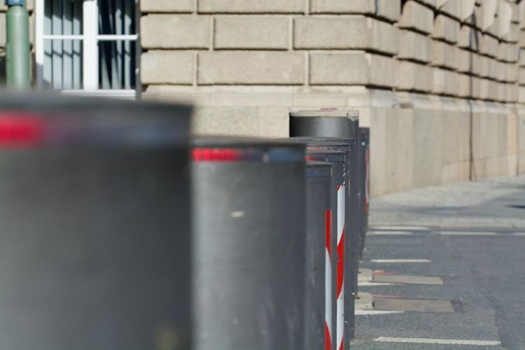 Close-up of garbage bin against wall in city