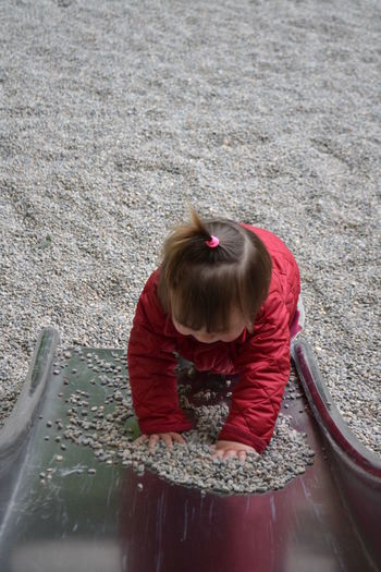 High angle view of girl playing with pebbles on slide