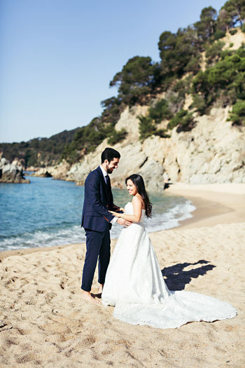 Newlywed couple enjoying at beach against clear sky during sunny day