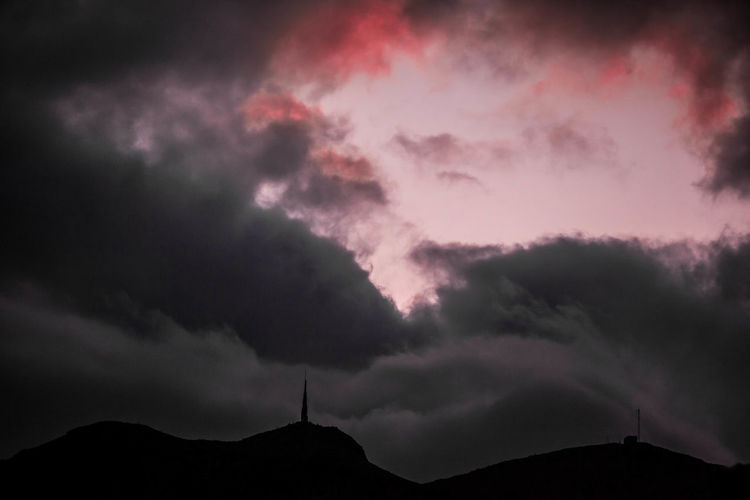 Low angle view of storm clouds over silhouette mountain