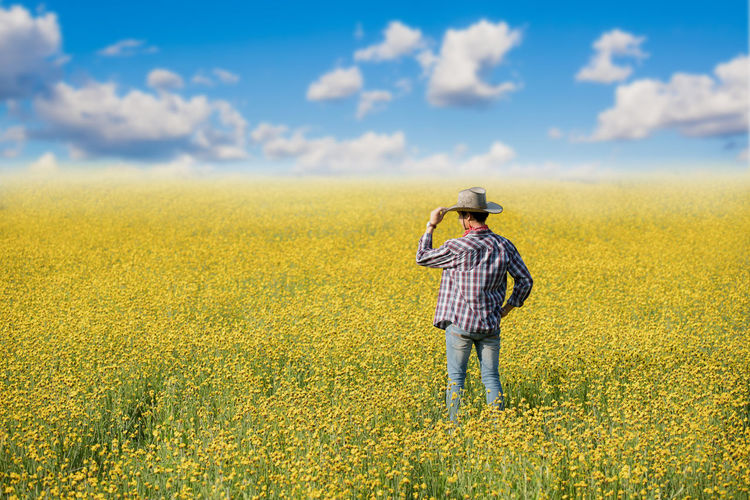Man Standing On Agricultural Field Against Sky