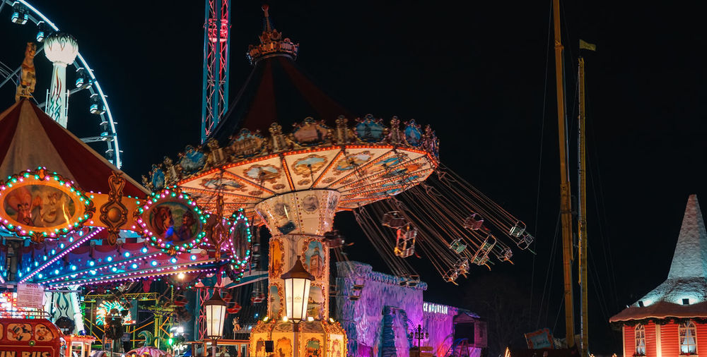 Low angle view of illuminated chain swing ride at night