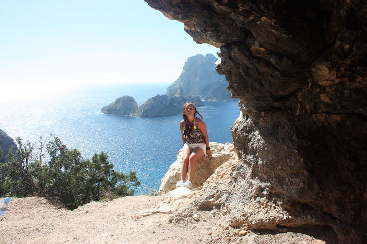 Girl on a cliff in front of the magical island of es vedra in cala d'hort in the ibiza island