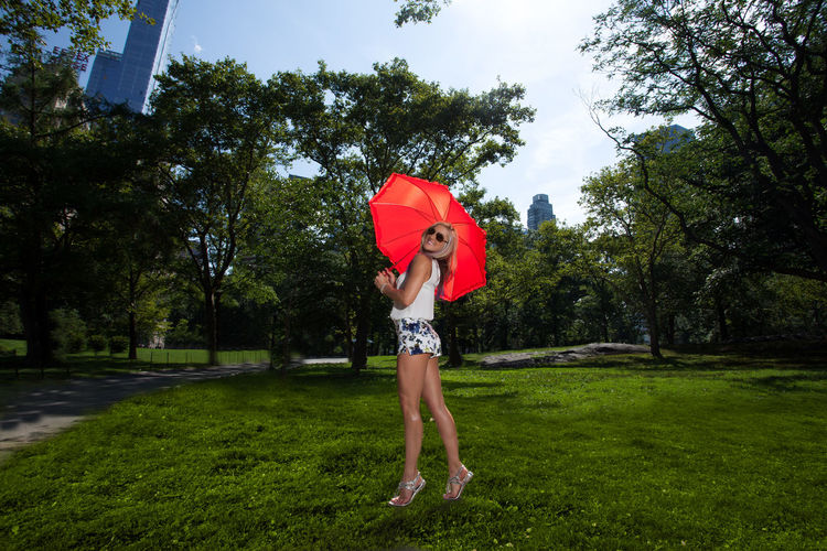 Full Length Of Woman Holding Umbrella While Standing At Park