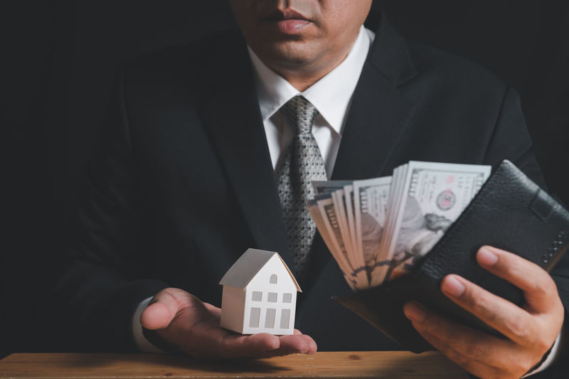 Businessman hold paper house model and check money in wallet