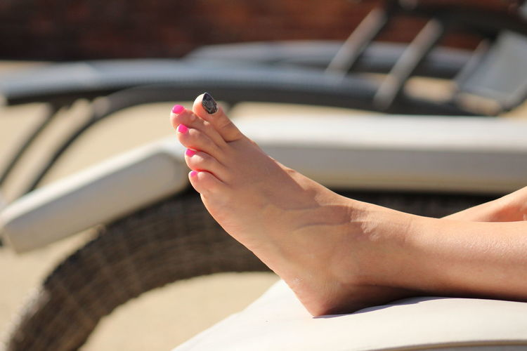 Low section of woman relaxing on lounge chair during sunny day