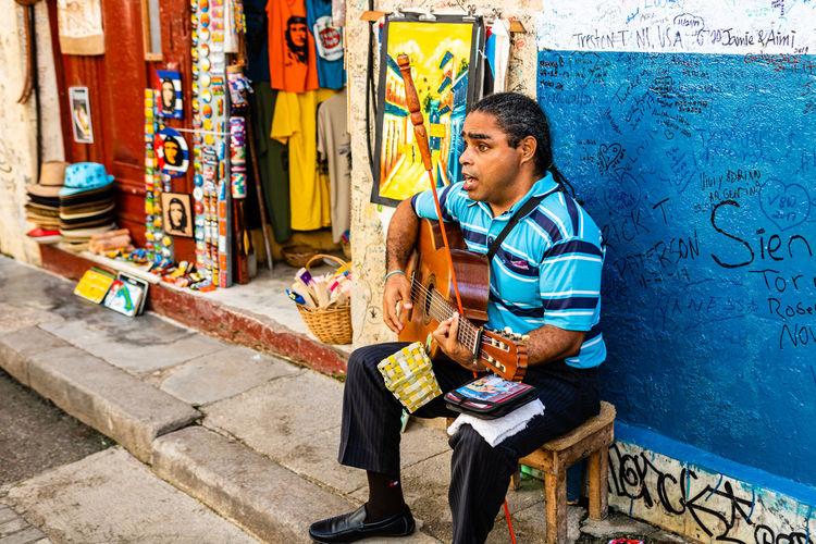 Full length of boy sitting by graffiti on wall