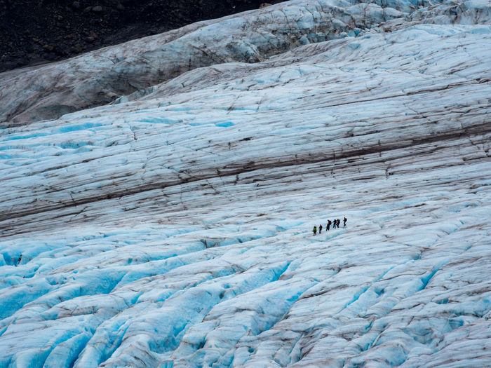 Hikers traversing the glacial ice of exit glacier in kenai fjords national park, alaska.