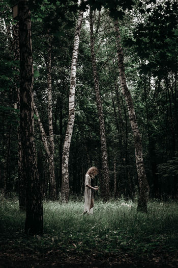 Lonely young woman standing alone in the middle of the forest