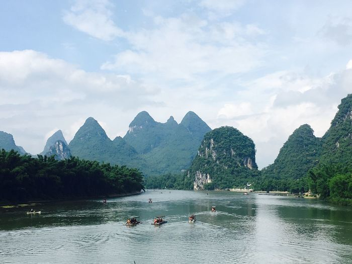 People in boats on river against mountains