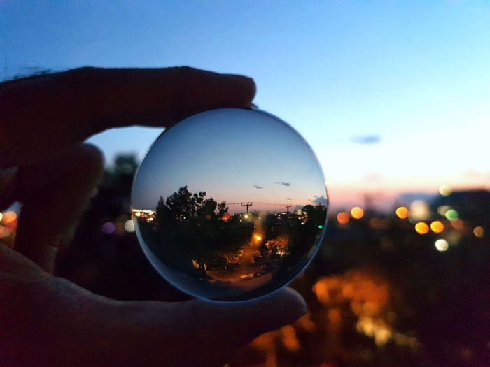Close-up of hand holding crystal ball against sky during sunset