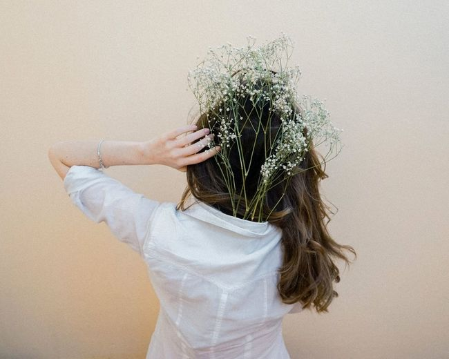 Rear view of woman wearing plants in shirt while standing against wall