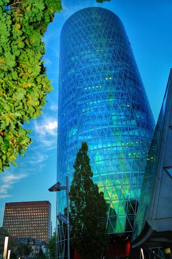 Round Skyscraper Modern Building Exterior Low Angle View Blue Sky White Clouds Modern Architecture Glass Office Building Outdoors Lens Flare Blue And Green After Sundown Westharbour Frankfurt Am Main Germany🇩🇪