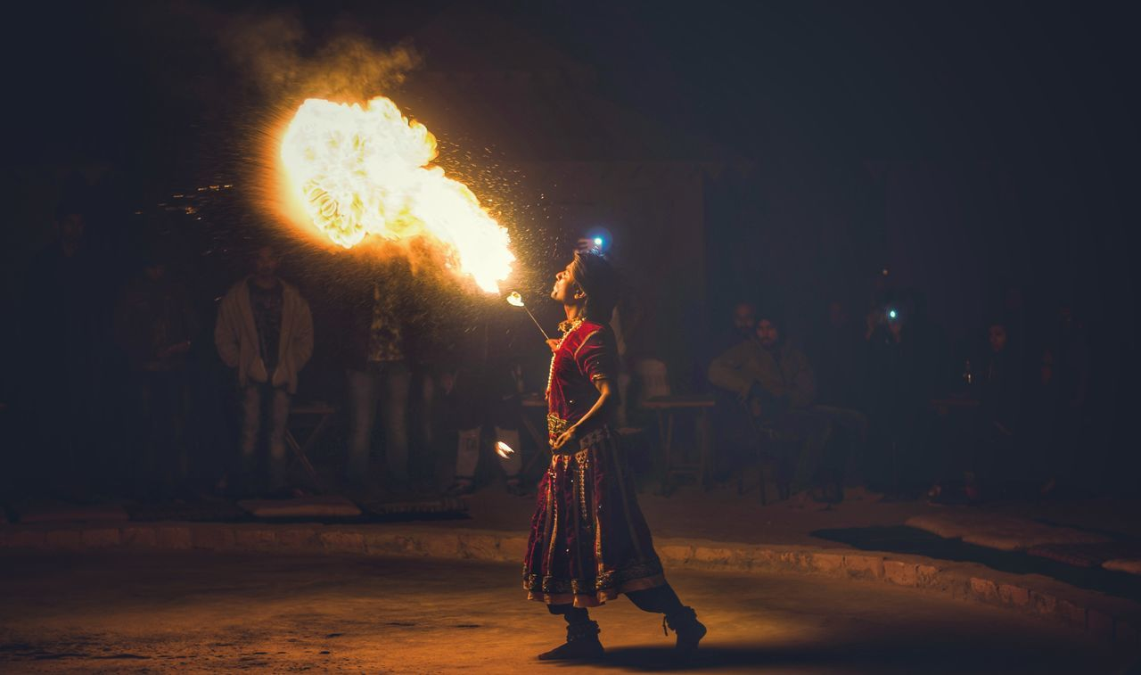 Fire-eater performing on street at night