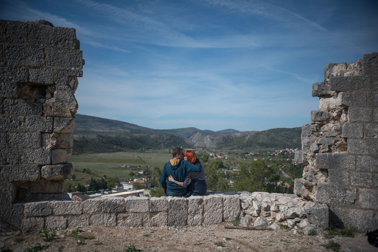 Couple Kissing While Sitting On Retaining Wall Against Sky