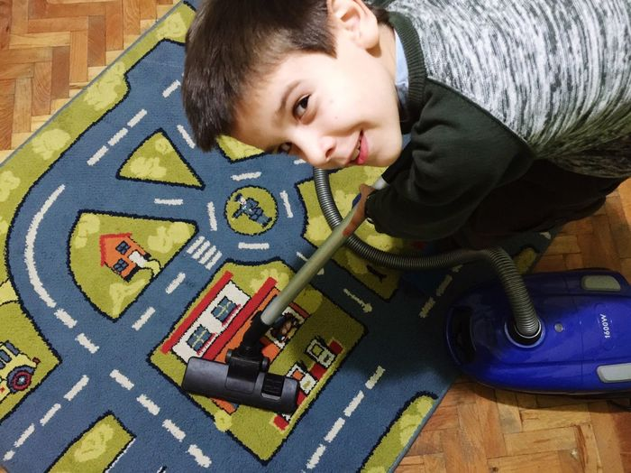 Portrait of boy cleaning carpet with vacuum cleaner