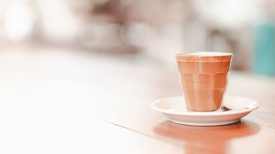 small cup of piccolo latte served on wooden table with copy space on right, monotone Bar Barista Beverage Bright Brown Cafe Caffeine Clean Coffee Copy Cup Drink Fresh Glass Hot Latte Milk Piccolo Relax Retro Serve Small Space Table Tone