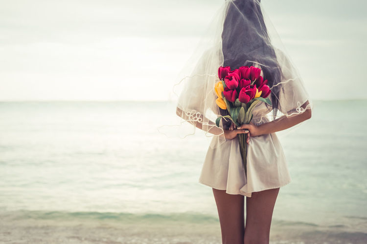 Rear View Of Woman Holding Bouquet While Standing At Beach Against Sky