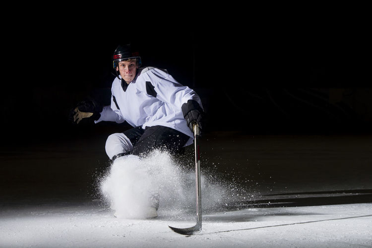 Portrait of man playing ice hockey against black background