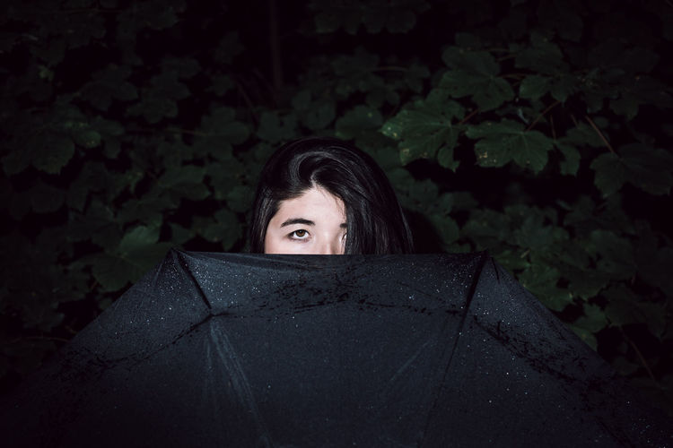 Portrait of woman with umbrella against tree at night
