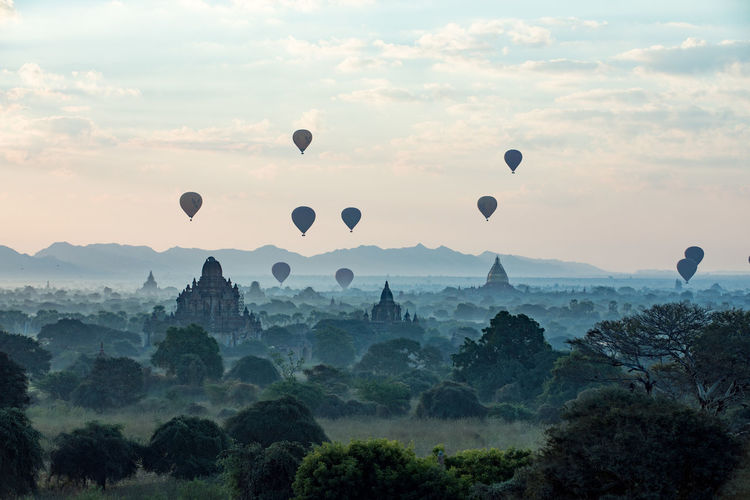 Silhouette hot air balloons over historic temple against sky