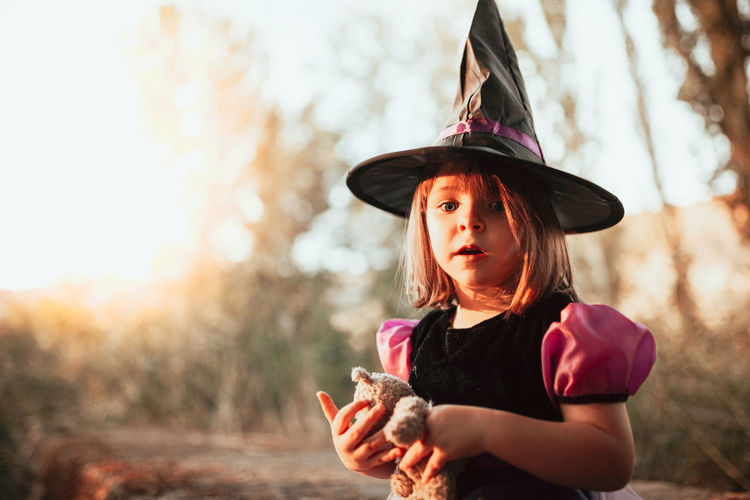 Portrait of girl wearing witchs hat during halloween at forest